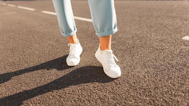Крупным планом женские ножки в синих винтажных штанах в стильных кожаных кроссовках на асфальте. модная женщина на прогулке в солнечный яркий летний день. современная сезонная коллекция стильных кроссовок.