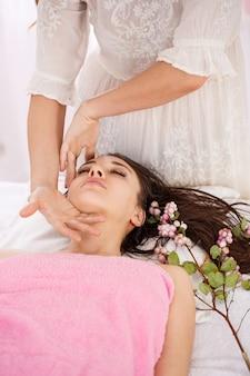 慎重に顔のマッサージをしている女性のマッサージ師の手のクローズアップ