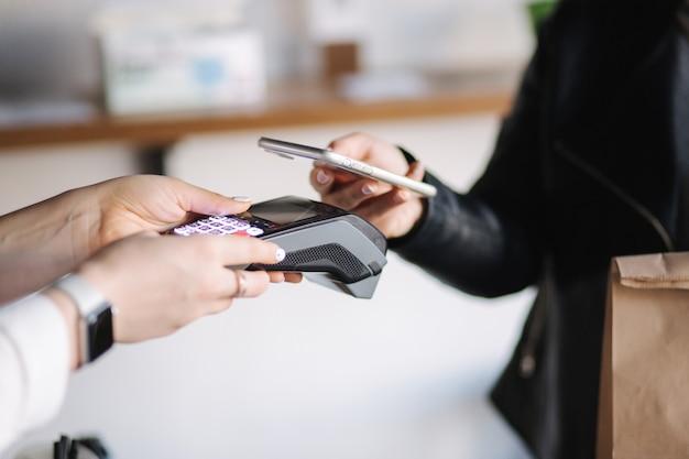 Крупным планом женщины платят с помощью смартфона