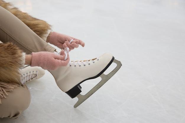 アイススケート場に座っていると靴ひもを結ぶ女性のクローズアップ