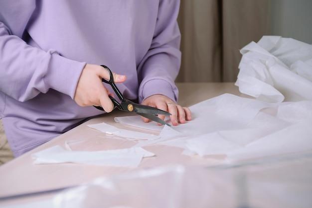 彼女のワークショップで紙の縫製パターンを切り取っている女性の仕立て屋のクローズアップ、選択的な焦点