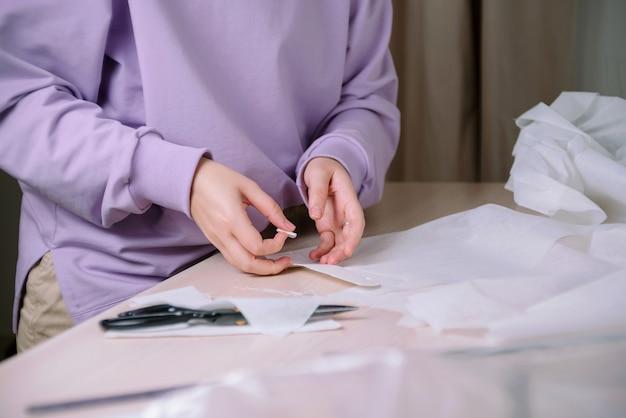 彼女のワークショップで紙の縫製パターンを扱う女性の仕立て屋のクローズアップ