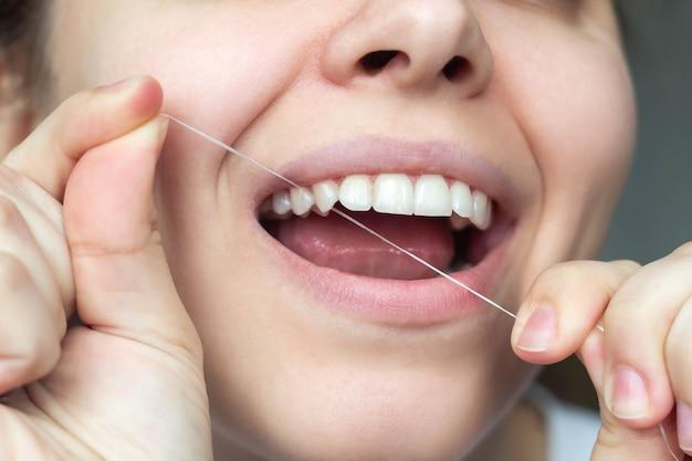 女性の歯のクローズアップ若い美しい女性がデンタルフロスで歯をきれいにするデンタルコンセプト