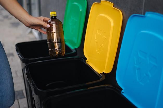 Крупным планом женщина бросает пластиковую бутылку в мусорное ведро разного цвета мусорных ведер