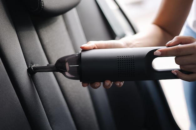 彼女の車の車のインテリア掃除の女性の掃除機でポータブル掃除機を使用して女性のクローズアップ