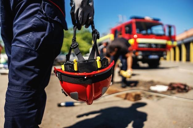 Крупным планом пожарный держит шлем и идет к пожарной машине.