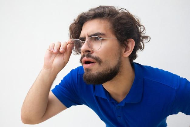 離れて見つめているメガネで集中して親切な男のクローズアップ