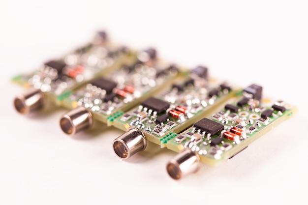 白いテーブルの上に横たわっているワイヤーの出力と4つの小さなマイクロ回路pcbのクローズアップ