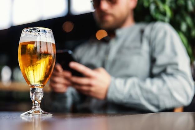 Крупным планом свежее холодное светлое пиво в стекле. на заднем плане мужчина пишет текстовое сообщение по телефону.