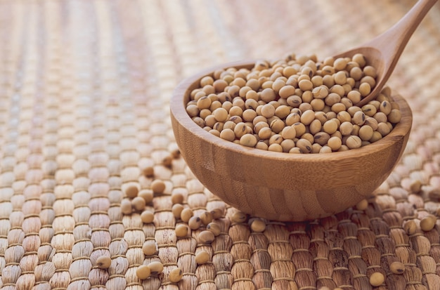 スプーンで木製のボウルに新鮮な乾燥大豆種子のクローズアップ
