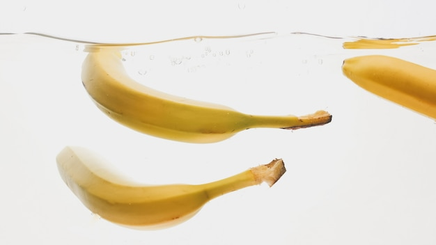 熟した新鮮なバナナが落下して水に飛び散るのクローズアップ
