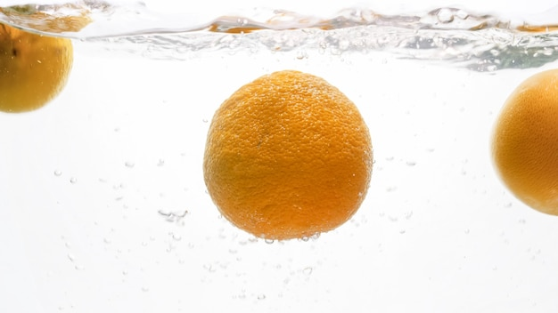新鮮な熟したオレンジが落下し、水しぶきのクローズアップ