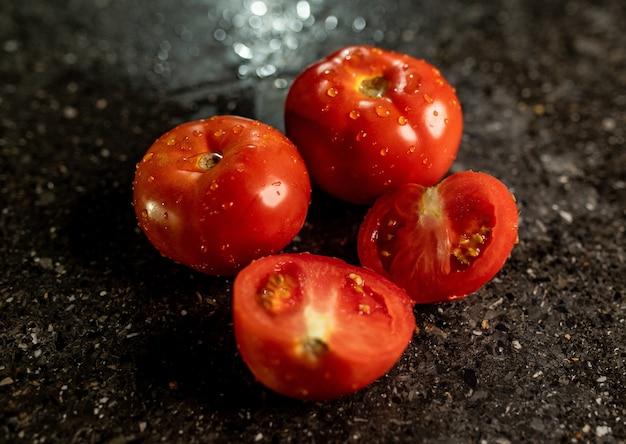 Крупным планом свежие спелые помидоры с каплями воды на поверхности кухонной стойки из черного гранита