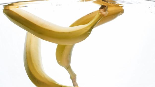 新鮮な熟した黄色いバナナが落ちて、澄んだ水に飛び散るのクローズアップ