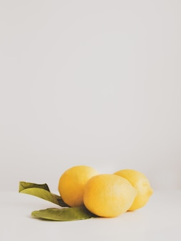 Крупным планом свежих спелых желтых лимонов с листьями на белом