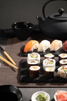 Крупный план свежих разнообразных суши на темном фоне. суши-сет и японский чай. вертикальный формат.