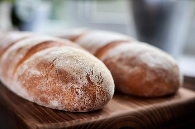 Крупным планом свежеиспеченные домашние хлебцы пшеницы на деревянных фоне