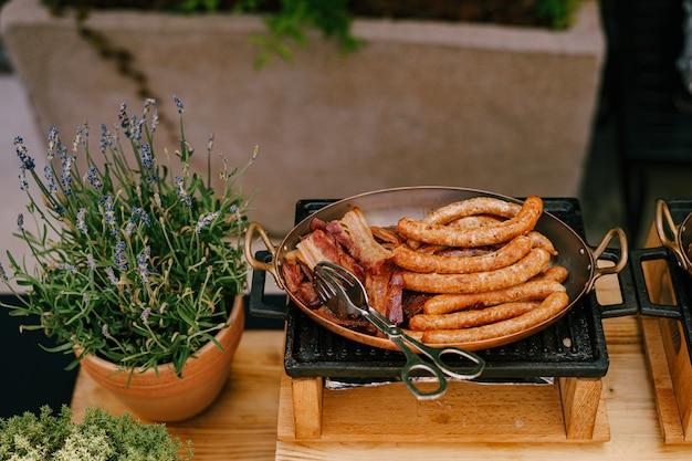 Крупным планом жареные сосиски на сковороде на чугунной плите с лавандой в цветочном горшке на