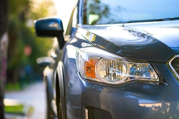 도시 거리 쪽에 주차된 깨끗한 새 차의 전면 헤드라이트를 닫습니다.