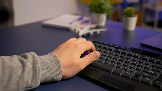 Крупным планом геймер печатает на профессиональной клавиатуре rgb, играя в онлайн-видеоигры в игровой домашней студии. игрок, использующий современное оборудование, транслирует соревнования по киберспорту поздно ночью