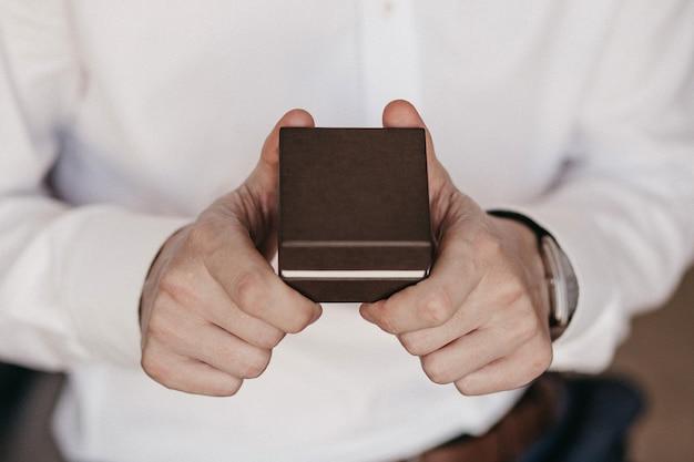 남성 손에 선물의 근접 촬영입니다. 흰 셔츠에 남자. 갈색 선물 상자를 들고 인식 할 수없는 남자. 특별한 날과 축제 이벤트 개념. 복사 공간 2 남자의 손입니다.