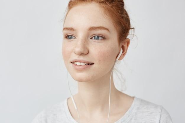 有線のイヤホンでストリーミング音楽を聴く生姜女性のクローズアップ。