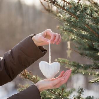 ニットのハートの装飾でクリスマスツリーを飾る女の子の手のクローズアップ
