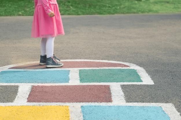 ピンクのドレスとアスファルトに描かれた石けり遊びで女の子の足のクローズアップ石けり遊びをしている子供
