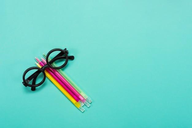 青い背景の上の眼鏡と色付きのペンのクローズアップあなたのテキストのための空きスペース