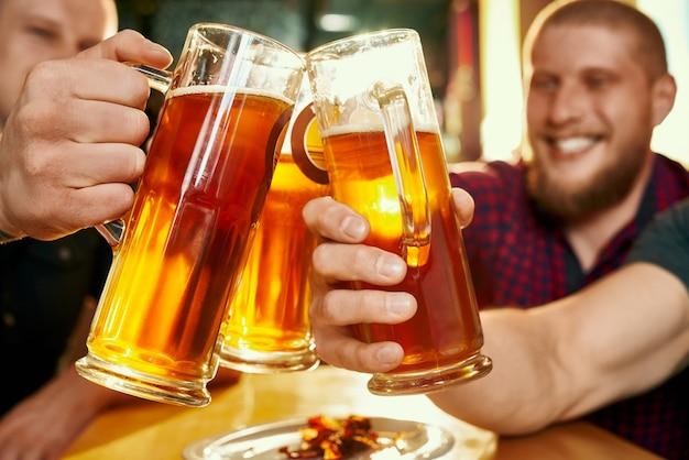 술집에서 행복 회사의 손에 맥주 잔의 근접 촬영. 명랑 한 남자 친구가 맥주 잔을 들고 주말에 술집에서 토스트하고 웃고 있습니다. 휴가 및 음료의 개념. 프리미엄 사진
