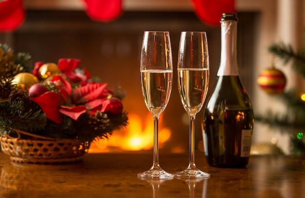 クリスマスのために装飾されたリビングルームで真夜中を示す古い時計の横にあるテーブルの上のシャンパングラスのクローズアップ