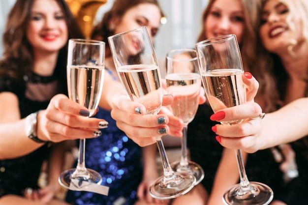 シャンパンとグラスのクローズアップ。特別な日を祝い、一緒に楽しんでいる若い女性。