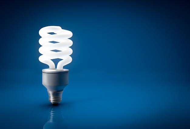 青色の背景に輝く省エネ電球のクローズ アップ