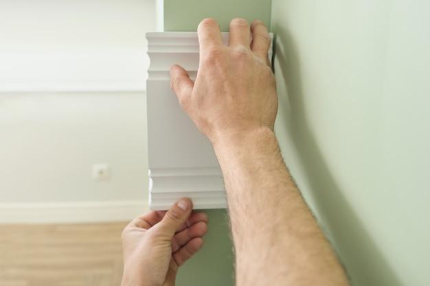 壁に木製の白い塗装板パネルを接着のクローズアップ