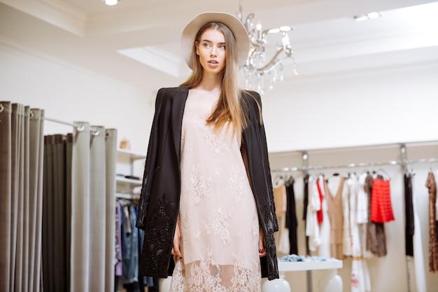 ドレス、ジャケット、帽子のゴージャスな若い女性のクローズアップはclothigストアに立っています