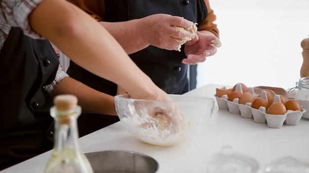 自家製の伝統的なクッキー生地を準備する孫娘の手のクローズアップ
