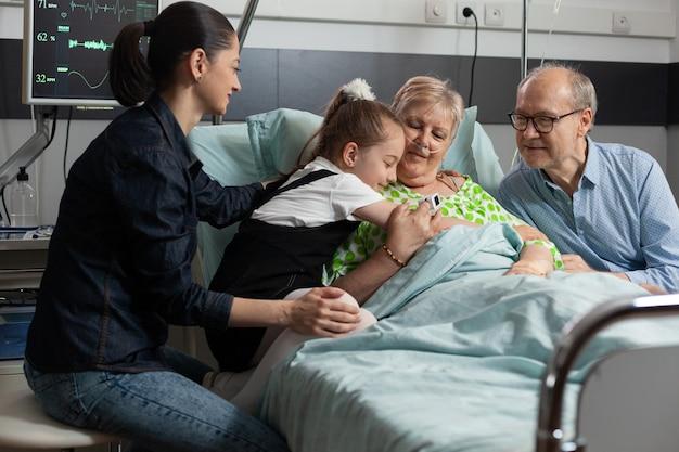 医学療法中に彼女を抱き締める祖母をサポートする孫娘のクローズアップ