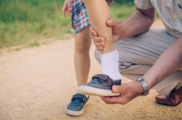 자연 경로 배경 위에 그의 손자에게 신발을 넣어 할아버지의 근접 촬영