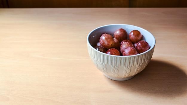 나무 테이블에 작은 그릇에 포도의 근접 촬영