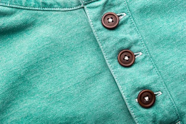 プラスチック製のボタンと緑の布のクローズアップ