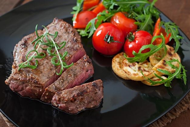Крупным планом на гриле стейк из говядины с овощами