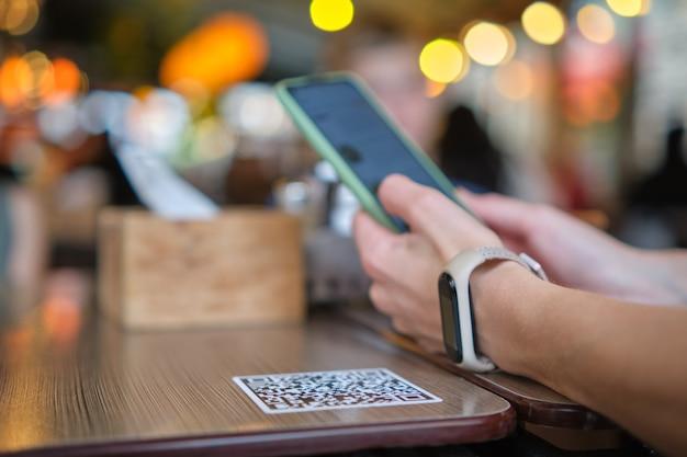 オンラインメニューの携帯電話でqrコードをスキャンしながらレストランで食事を注文するゲストの手のクローズアップ。