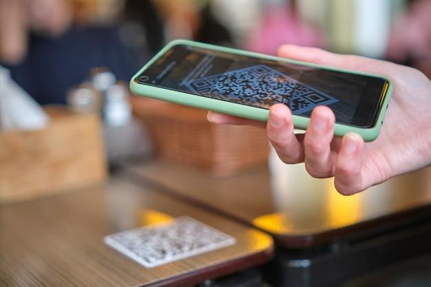 온라인 메뉴를 위해 휴대전화로 qr 코드를 스캔하는 동안 레스토랑에서 손님이 손으로 식사를 주문하는 것을 닫습니다.