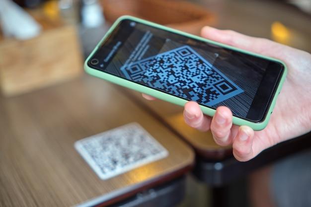온라인 메뉴를 위해 휴대전화로 qr 코드를 스캔하는 동안 레스토랑에서 손님이 식사를 주문하는 것을 클로즈업합니다.