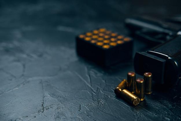 Крупным планом рукоятка пистолета и пули на бетонном столе огнестрельное оружие и концепция боеприпасов защиты или в ...