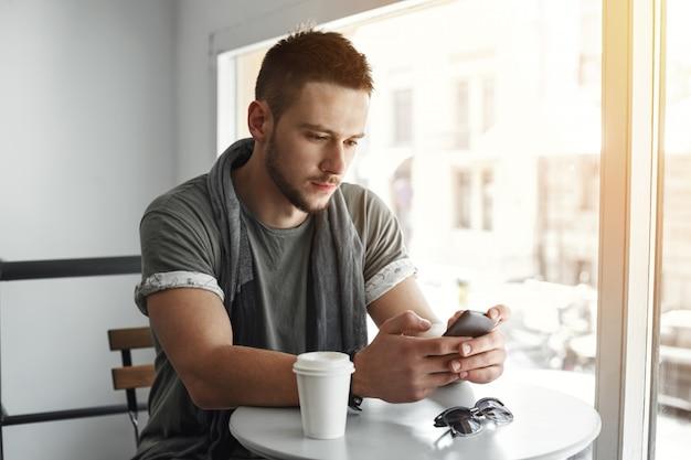 Крупный план парня сидя на таблице в кафе, отправляя смс сообщении.