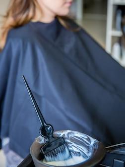 그릇에 염색약을 닫고 백그라운드에서 여성 고객과 머리 색깔을 바꿀 준비가 된 브러시