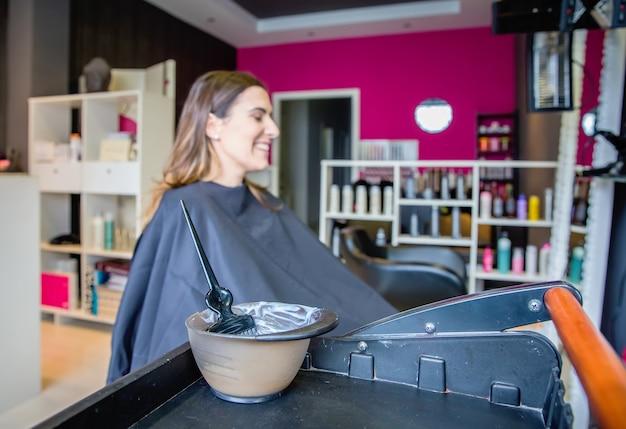 여성 고객과 함께 머리 색깔을 바꿀 준비가 된 그릇과 브러시에 염색약을 닫습니다