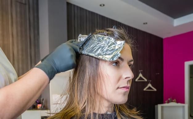 머리 색깔을 바꾸기 전에 알루미늄 호일로 아름다운 젊은 여성의 머리카락을 감싸는 미용사 손