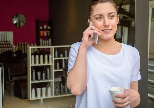 헤어 및 뷰티 살롱에서 커피를 마시며 스마트폰으로 이야기하는 미용사 여성의 클로즈업